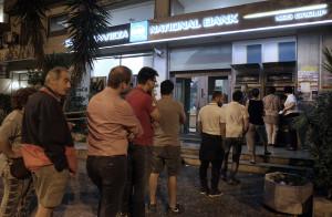 Πολίτες περιμένουν έξω από ΑΤΜ τράπεζας στην Αθήνα για να κάνουν ανάληψη χρημάτων ξημερώματα Σαββάτου 27 Ιουνίου 2015, μετά την ανακοίνωση από τον πρωθυπουργό Αλέξη Τσίπρα για τη διενέργεια δημοψηφίσματος την Κυριακή 5 Ιουλίου για την αποδοχή ή την απόρριψη της πρότασης των θεσμών.